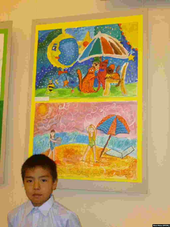 Участник экспериментальной выставки девятилетний Нуржан Зейтен, фотографируется на фоне своей работы «Дружная компания», выполненной гуашью. На выставке была вся его семья.