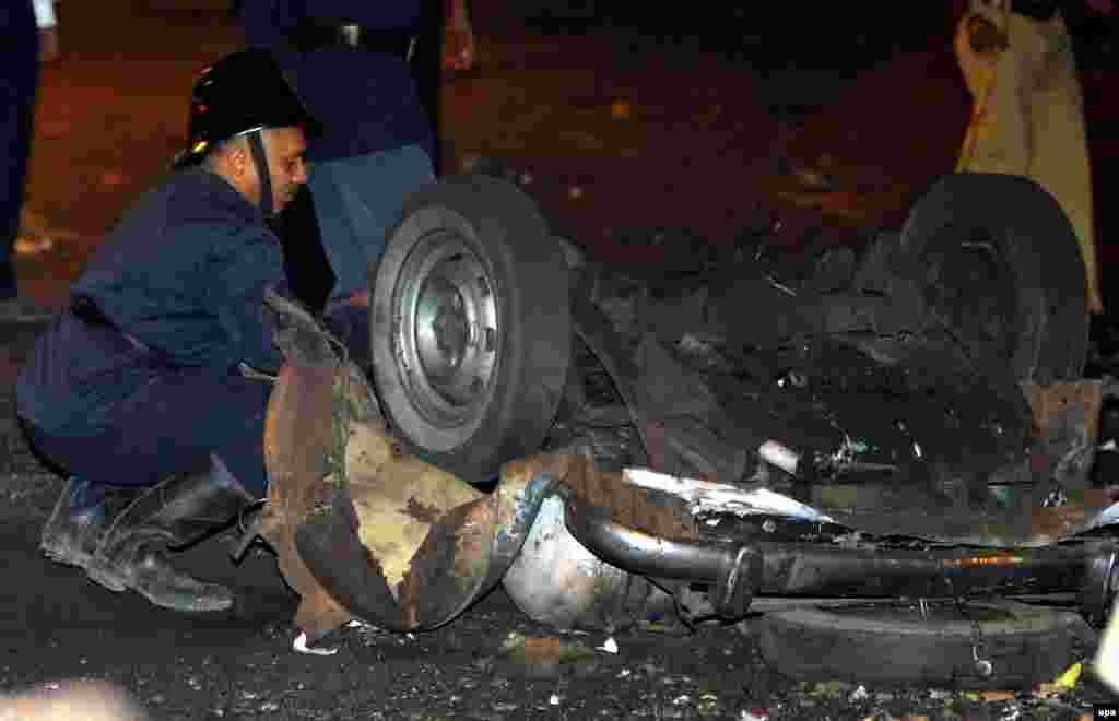 Полицейский исследует место взрыва автомобиля в Мумбаи, вечер 26 ноября 2008.