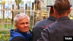 Юрий Петровский, обвиняемый в организации акции в московском храме Христа Спасителя, в сопровождении полиции.