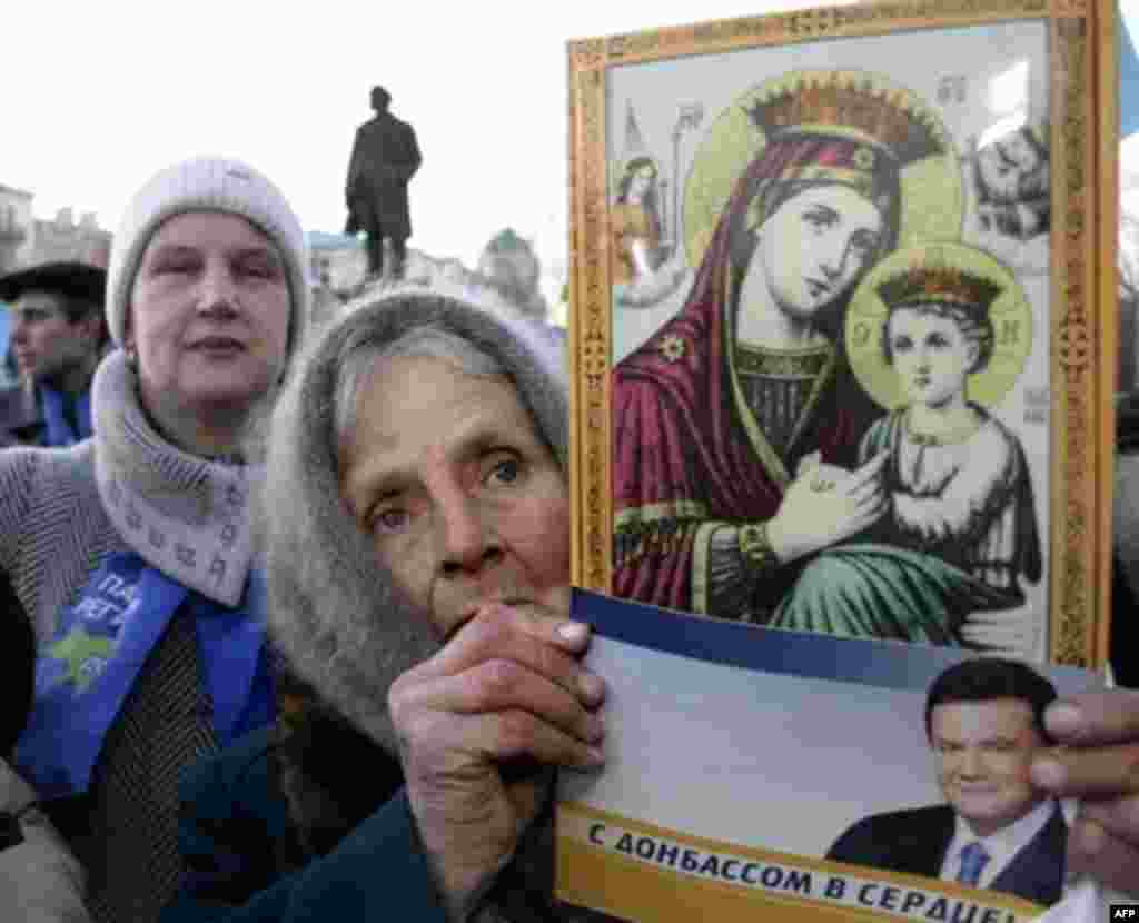 "An elderly woman in the heart of the Donbas, Donestsk, holds a flyer for Viktor Yanukovych that reads ""With the Donbass in my heart!"" (AFP) - In elections in March, the party of Ukrainian President Viktor Yushchenko was trounced. But with the Yuliya Tymoshenko Bloc topping the vote, an Orange government seemed possible. But a last-ditch deal collapsed, bringing to power Viktor Yanukovych, the man whose rigged presidential victory prompted the Orange Revolution."