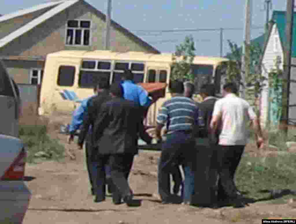 Family and acquaintances carry alleged suicide bomber Rahimjan Makhatov's remains, wrapped in a carpet, to prepare them for burial in his hometown of Aqtobe.