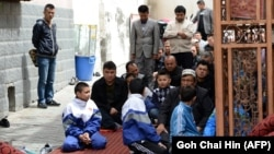 Uyghur children join the adults at a mosque for Friday Prayers in Urumqi, the capital of Xinjiang.