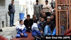 Дети и взрослые на пятничной молитве в Урумчи, провинция Синьцзян