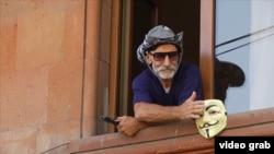 Один из вооруженных людей, захвативших здание полиции в районе Эребуни, стоит в проеме окна. Ереван, 27 июля 2016 года.
