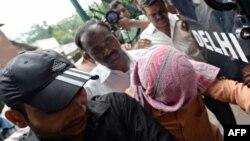 Үнді полицейлері айып тағылған жасөспірімді (басын бүркеп алған) сот залына әкеле жатыр. Нью-Дели, 25 шілде 2013 жыл.