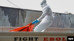 Liberia -- A Liberian health worker in a burial squad drags an Ebola victim's body for cremation from the ELWA treatment center in Monrovia, October 13, 2014