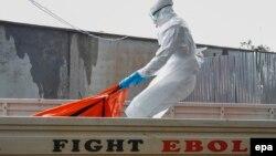 Либерия: работник столичной больницы переносит в крематорий тело умершего от Эболы. Монровия, 13 октября 2014 г.