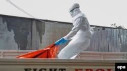 Медработник с телом погибшего от лихорадки Эбола в Монровии, Либерия.