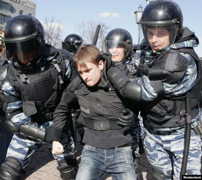 Police detain a young antigovernment protester at Pushkin Square on March 26.