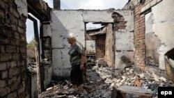 Женщина стоит посреди разрушенного дома. Село Александровка близ Донецка, 27 августа 2015 года.