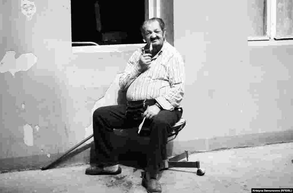Jan Batiy enjoys his favorite pipe, which he says is one of his few remaining pleasures since his walking is now limited. He reminisces about the old days from his post in the courtyard.