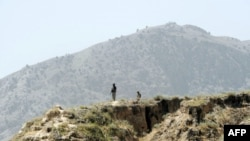 Pakistani soldiers stand guard on a mountain ridge in the tribal district of Mohmand.