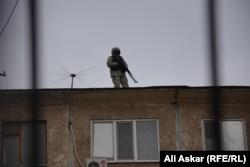 Вооруженный сотрудник спецслужбы стоит на крыше здания суда в день слушаний по делу о вооруженных нападениях 5 июня в Актобе. 18 октября 2016 года.