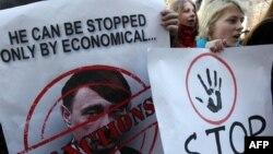 Украинские активисты держат в руках плакат с изображением президента России Владимира Путина, нарисованного в образе Адольфа Гитлера. Киев, 11 марта 2014 года.