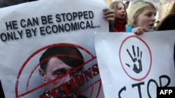 An activist in Kyiv holds a poster of Russian President Vladimir Putin caricatured as Adolf Hitler.