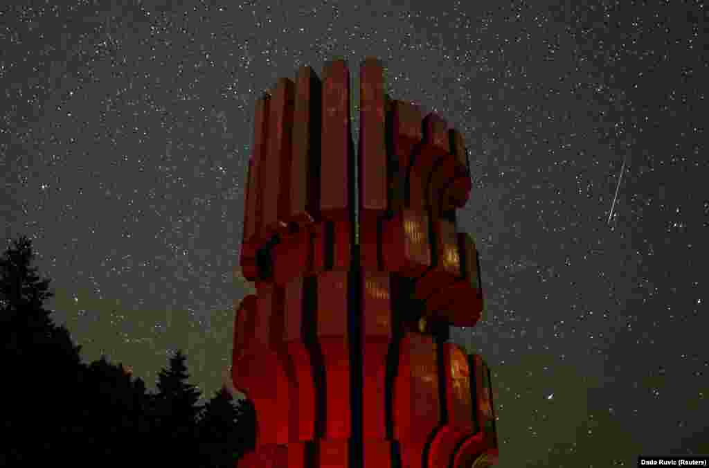 A meteor streaks across the sky near the Monument to the Revolution, a World War II memorial in Mrakovica, Bosnia. (Reuters/Dado Ruvic)