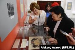 Одна из фотографий с выставки. Дочь Алькея Маргулана Данель (справа) осматривает экспозицию выставки. Казахстан, Алматы, 12 июня 2019 года.