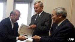 Ирандын тышкы иштер министри Манучер Моттаки (солдо) Тегерандын сунуштарын 6 өлкөнүн өкүлдөрүнө тапшырып жаткан учур. Тегеран 9-сентябрь 2009-жыл
