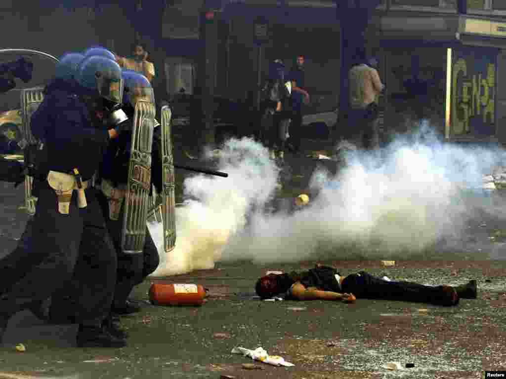 Riot police storm past a dead protester who has been shot and killed by Carabiniere during rioting in central Genoa July 20, 2001. Police fired tear gas and used water cannon in an attempt to disperse thousands of protesters demonstrating against the G8 summit. REUTERS/Dylan Martinez