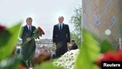 Владимир Путин (П) и Шавкат Мирзиёев (Л) возлагают цветы к могиле Ислама Каримова в Самарканде. Узбекистан, 6 сентября 2016 года