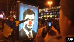 Киевдин ортолук майданындагы протестчи президент Януковичтин бети боёлгон портретинин жанында. 3-декабрь, 2013.