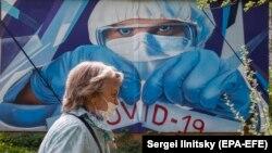 Женщина идет мимо граффити, изображающего медицинского работника. Россия, Московская область. 15 мая 2020 года.