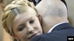 Yulia Tymoshenko is embraced by her husband Oleksandr after her conviction is announced.