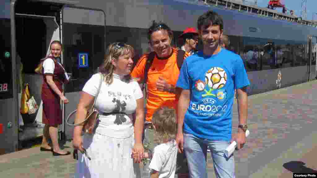 Irina Toldina, a 31-year-old lawyer from Kharkiv, her husband, Oleg (right), and son Yaroslav, 5, welcome visiting Dutch fan John, who came to Kharkiv for the Netherlands vs. Denmark match on June 9.