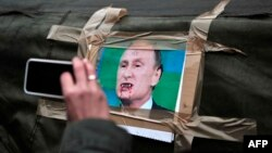 Russian President Vladimir Putin's snarling visage has become the main target for caricatures and cartoons.