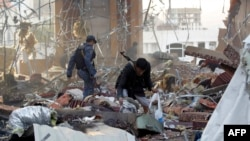 A Yemeni collects items amid the rubble of a destroyed building following reported air strikes by Saudi-led coalition airplanes on the capital Sanaa on October 8.