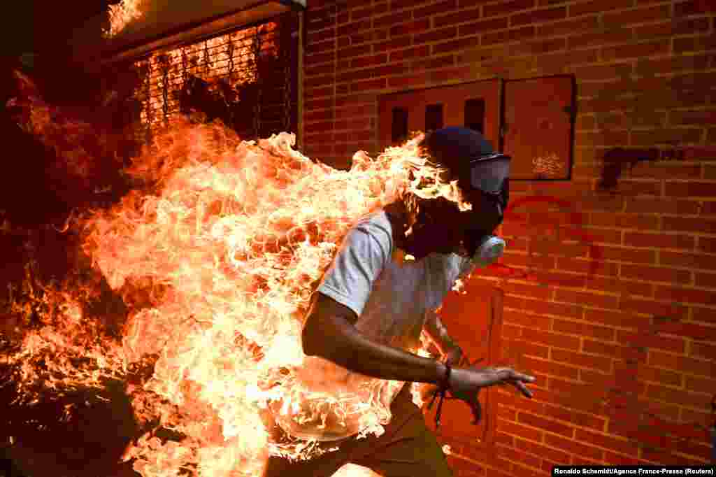The World Press Photo of the Year shows 28-year-old Jose Victor Salazar Balza catching fire amid violent clashes with riot police during a protest against President Nicolas Maduro, in Caracas, Venezuela.