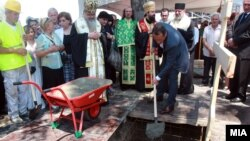 Russian businessman Sergei Samsonenko (holding shovel) helps lay the cornerstone for the Holy Trinity Russian Orthodox church in Skopje.