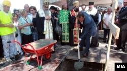 Russian businessman Sergei Samsonenko (holding shovel) helps lay the cornerstone for the Holy Trinity Russian Orthodox church in Skopje.