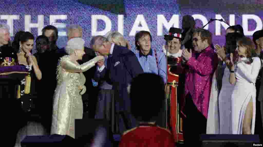 """Принц Чарлз целует руку матери, Королевы Великобритании, на концерте, посвященном бриллиантовому юбилею правления Елизаветы II в Букингемском дворце в Лондоне 4 июня. На концерте в честь 60-летия на троне выступили мировые """"звезды"""", включая Пола Маккартни, Стиви Вандера и Элтона Джона. (Reuters/Дэвид Мойр)"""