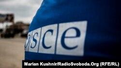 Луганск вилоятидаги кузатувчилардан бирининг камзули орқасидаги ЕХҲТ логотипи.