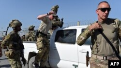 FILE: U.S. soldiers leave a truck inside an Afghan military base during fighting between Taliban militants and Afghan security forces in the northeastern city of Kunduz in 2015.