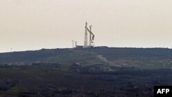 The flag of the Syrian Kurdish People's Protection Units (YPG) flies in the Syrian town of Kobani of January 26.