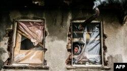 لاجئة سورية تنظر من خلال نافذة بلا زجاج - اسطنبول 4 آذار 2014
