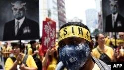 معترضات تصاویری از رزاق به شکل ابلیس در دست دارند