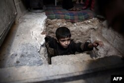A Syrian boy climbs out of a bomb shelter in the rebel-held town of Douma, on the eastern outskirts of Damascus, on October 30.