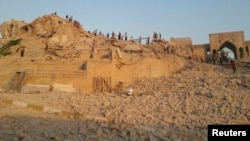 """Ирак -- """"Ислам мамлекети"""" тобунун бомбалоосунан кыйраган Жунус пайгамбардын мечитинин урандыларынын арасында жүргөн адамдар. Мосул, 24-июль, 2014."""