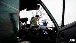 Ресейшіл сепаратист пен ЕҚЫҰ бақылаушысы бүлінген көлік жанында тұр. Широкино селосы, 30 наурыз 2015 жыл. (Көрнекі сурет)