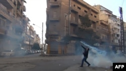 A tear-gas canister is thrown back toward security forces in Homs in late December.