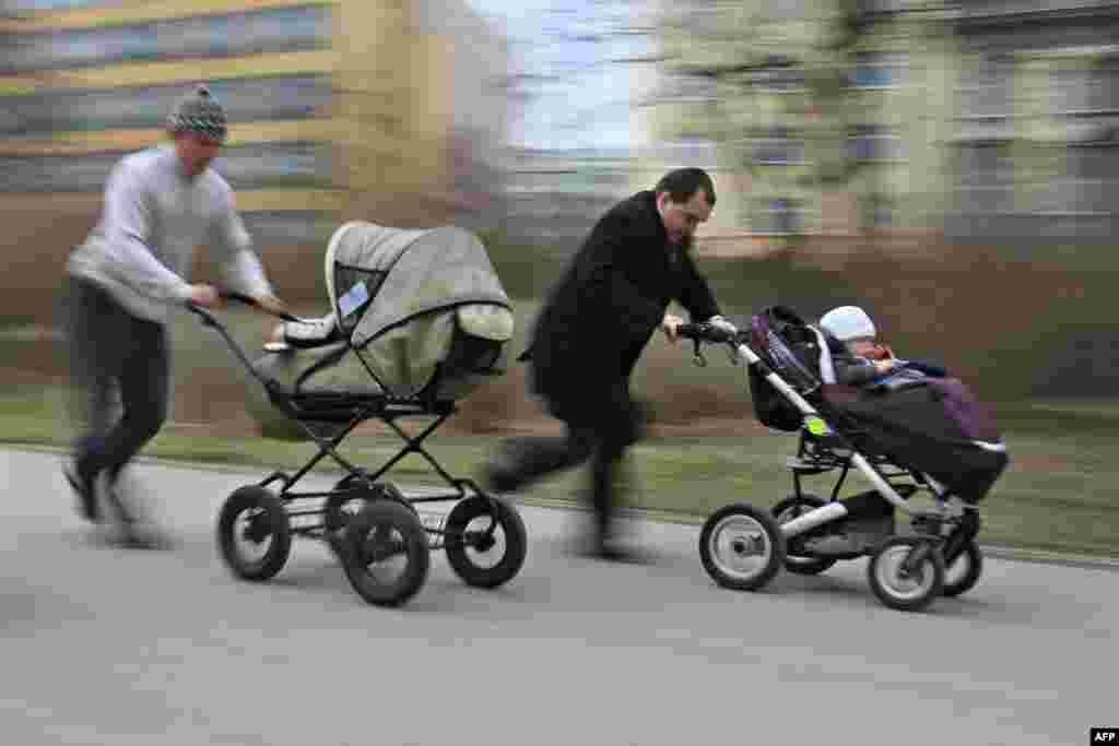 Two men push their children in a stroller during a race-walking competition in Brno, Czech Republic, on World Health Day. The Stroller Racing World Health Day event was celebrated in 25 different locations in the Czech Republic, with competitions for mothers, fathers, and the entire family. (AFP/Radek Mica)