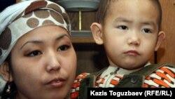 Асем Кенжебаева, дочь погибшего Базарбая Кенжебаева, с сыном. Поселок Кызылсай Мангистауской области. 14 февраля 2012 года.