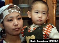 Дочь погибшего от пыток в Жанаозене Базарбая Кенжебаева - Асем Кенжебаева со своим трехлетним сыном Ануаром. Поселок Кызылсай Мангистауской области. 14 февраля 2012 года.