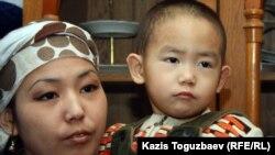 Дочь погибшего Базарбая Кенжебаева, Асем со своим трехлетним сыном Ануаром. Поселок Кызылсай Мангистауской области. 14 февраля 2012 года.