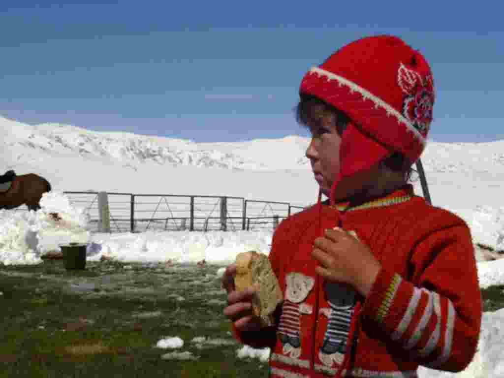 A child in Naryn is bundled up for unseasonable weather.