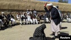 """Афганский судья наносит удары плетью """"провинившейся"""" женщине в провинции Гор. 31 августа 2015 года."""