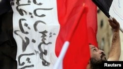 A protester holds an Egyptian flag during a protest in Cairo in early February.